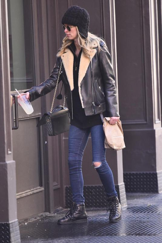 Nicky Hilton wearing a black shearling Moto jacket, black sweater, dark wash skinny jeans with knee rips, black lace up winter boots, and a black quilted handbag