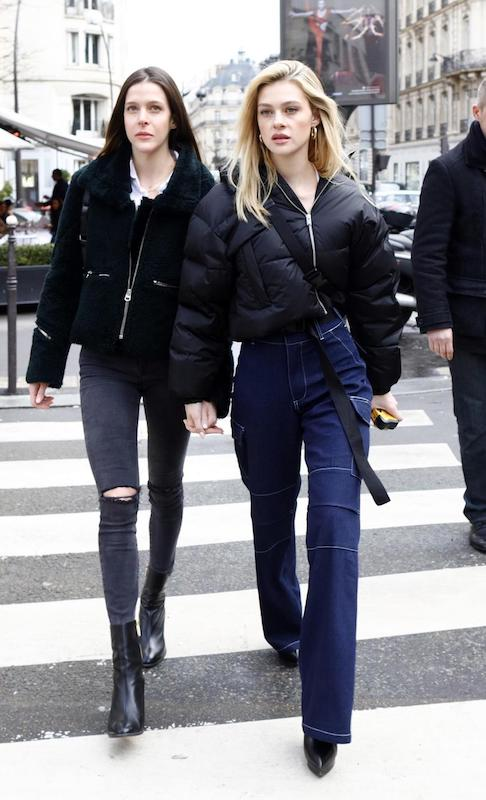 Nicola Peltz wearing a black cropped puffer jacket, white square neck cropped t-shirt, wide-leg cargo jeans, black platform ankle booties, and a black bum bag