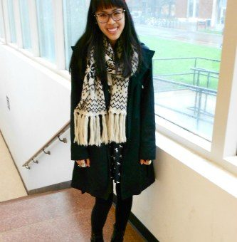 College street style at Oregon State University: Student fashionista wearing a fair isle scarf, glasses, tights, a pea coat, a cat print dress, boots, and a pink hair bow