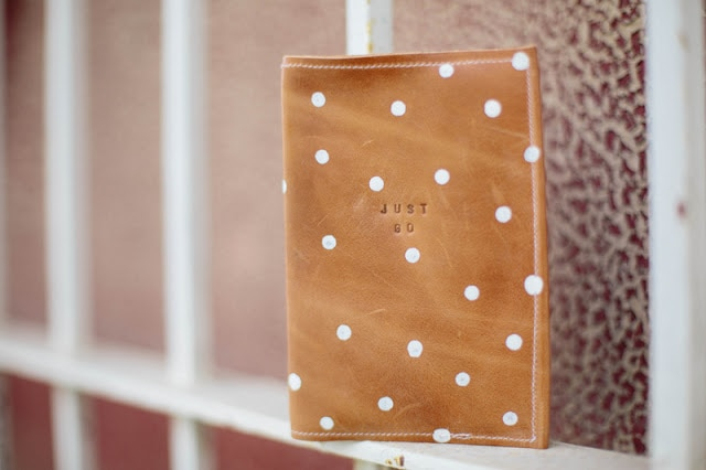 Photo containing leather passport holder with white polka dots.