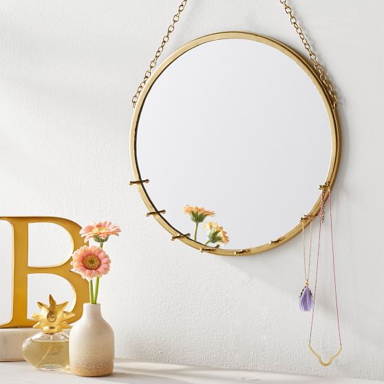 PB Teen round brushed gold hanging mirror with pins for necklaces.