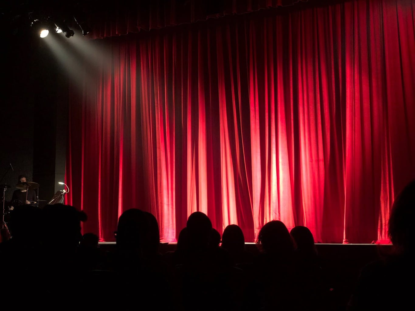 People at a theater with a red curtain and lights