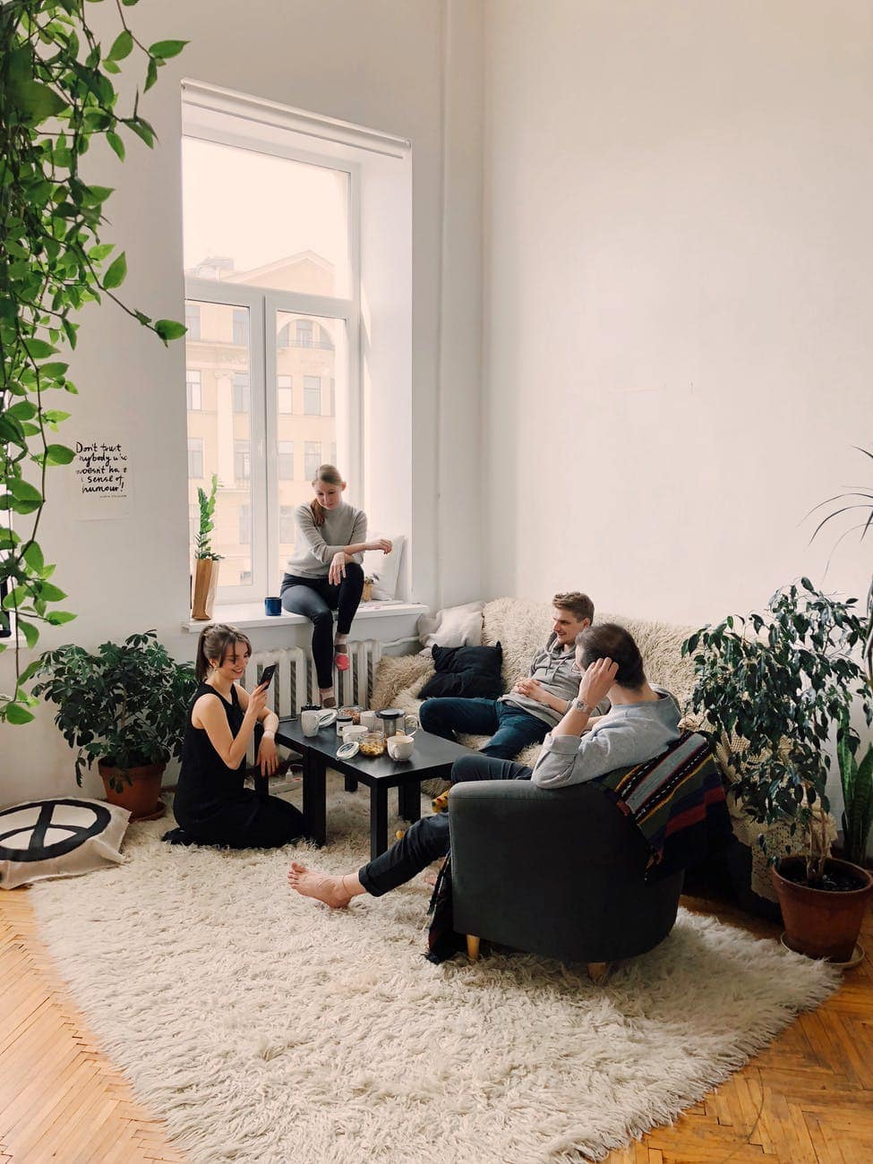 People gathered inside a living room with lots of plants