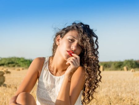 girl with curly hair in field