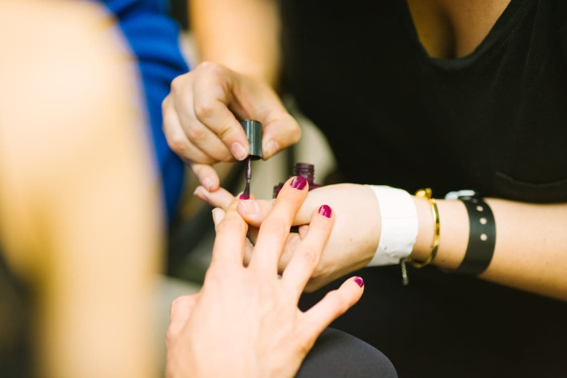 woman in black shirt painting nails