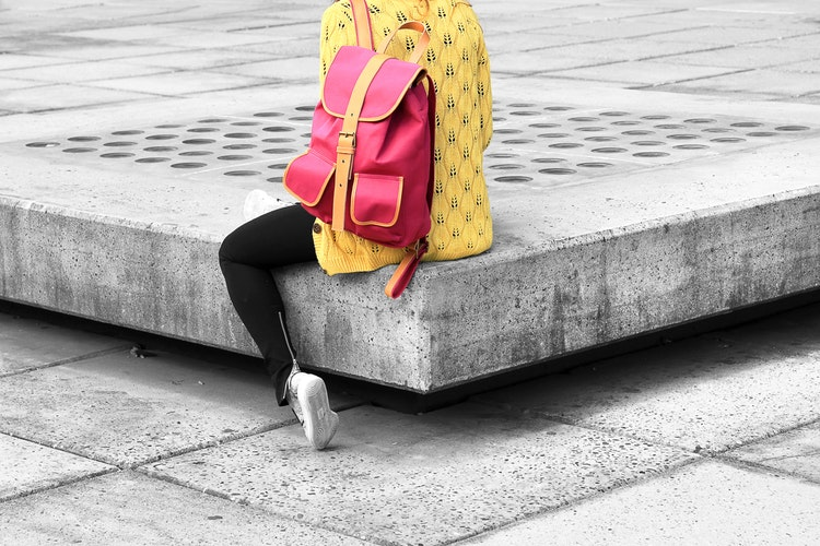 Women sitting on public bench with bright red backpack