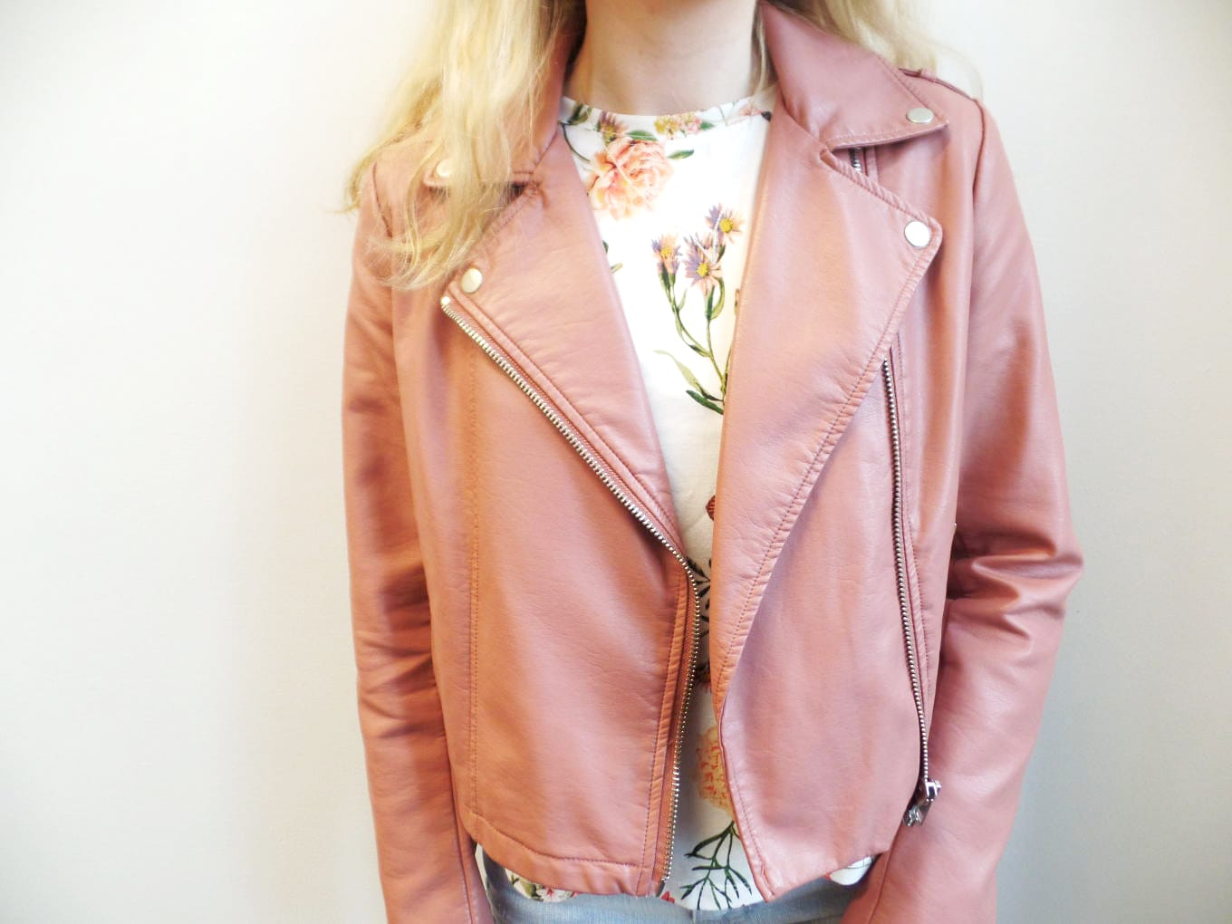 Veronica wears a dusty rose faux leather motorcycle jacket with a white floral shirt.