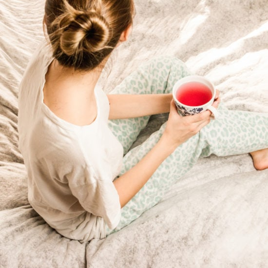 Image of young woman with her hair in a bun sitting on a bed wearing pajamas and holding a drink in a cup, with her head turned away from the camera