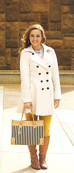 Point Park University fashion - student wearing a white pea coat, mustard yellow jeans, striped bag, camel boots