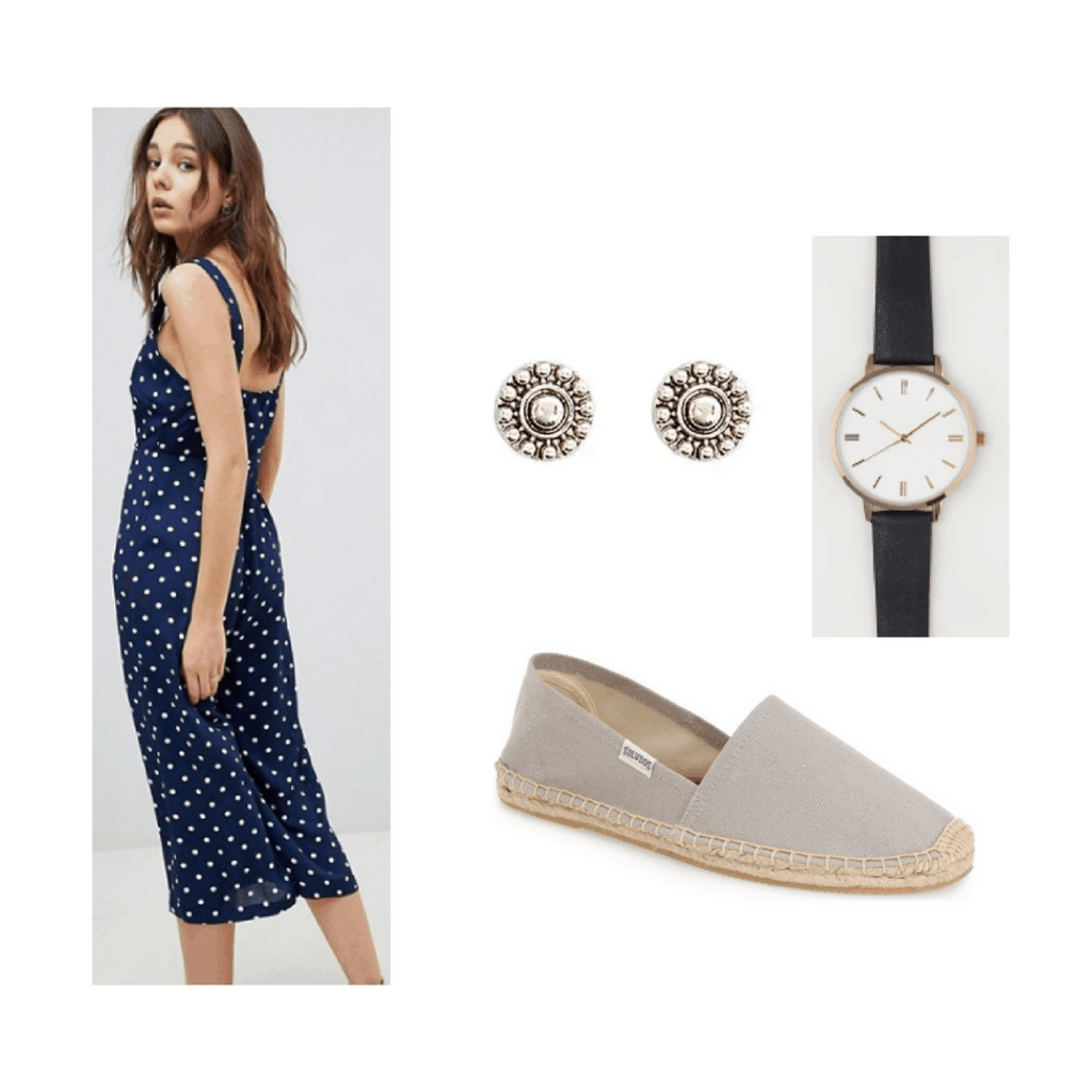 blue polka dotted jumpsuit with earrings, black watch and grey shoes