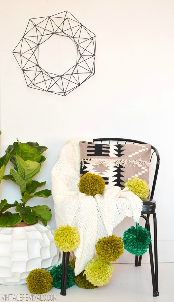 Photo including a chair with a pom pom blanket in it as well as a pillow. There is a plant to the left of the chair and a metal wall hanging above it.