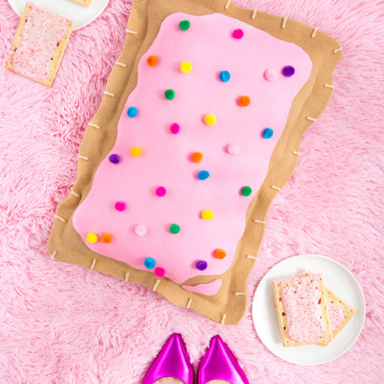 Picture of four strawberry pop-tarts, a pink fur rug, pointed block heels, and a pop-tart pillow.