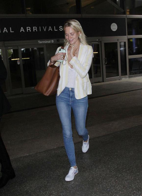 Poppy Delevingne wearing a yellow and white striped blazer, a white t-shirt, skinny jeans, a brown oversized tote bag, and white low-top sneakers