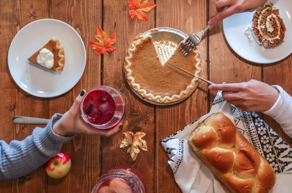 Woman cutting into pumpkin pie with bread, drinks, and dessert for Thanksgiving