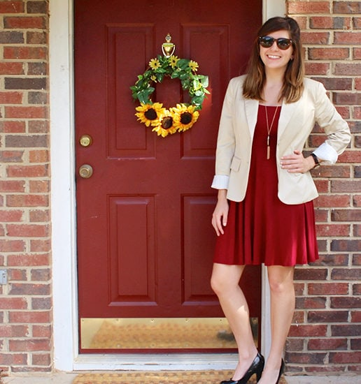 Leah wearing a red dress and tan blazer by a red door.
