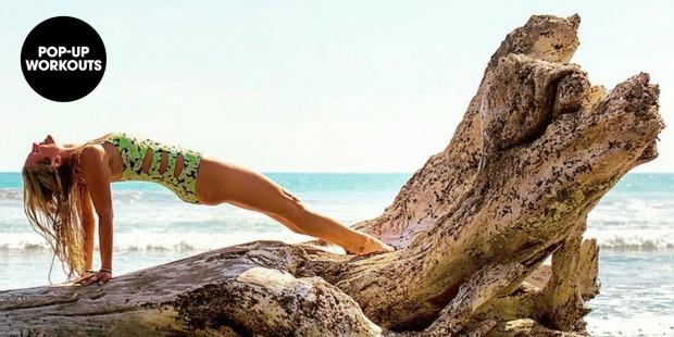 Girl doing a reverse plank on a beach