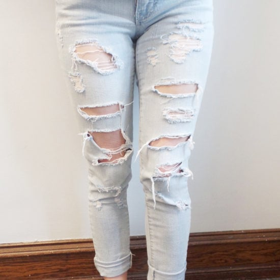 Veronica's jeans are light-wash and ultra distressed. She wears them cuffed to show off her high-top white Converse shoes.