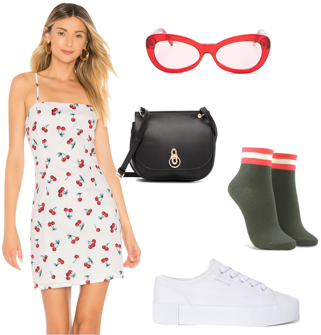 Rita Ora Outfit: cherry print mini dress, black crossbody bag, red tinted oval sunglasses, red and white striped ankle socks, and white low top sneakers