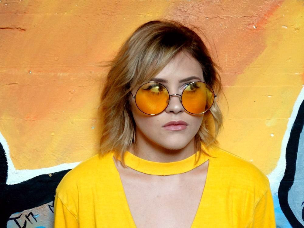 College student fashion at WVU: Shelby wears a yellow cutout tee shirt and round yellow sunglasses
