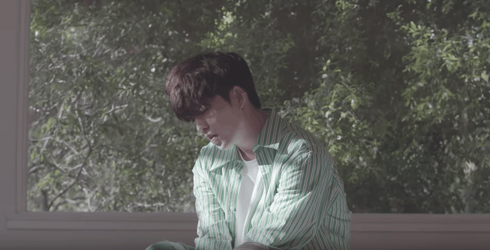 Seventeen kpop fashion: Don't Wanna Cry music video. Member wears green striped shirt in front of a window.
