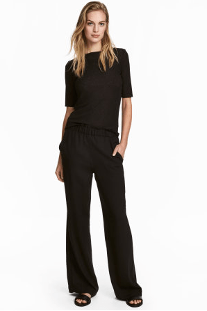 woman in wide legs pants and black shirt