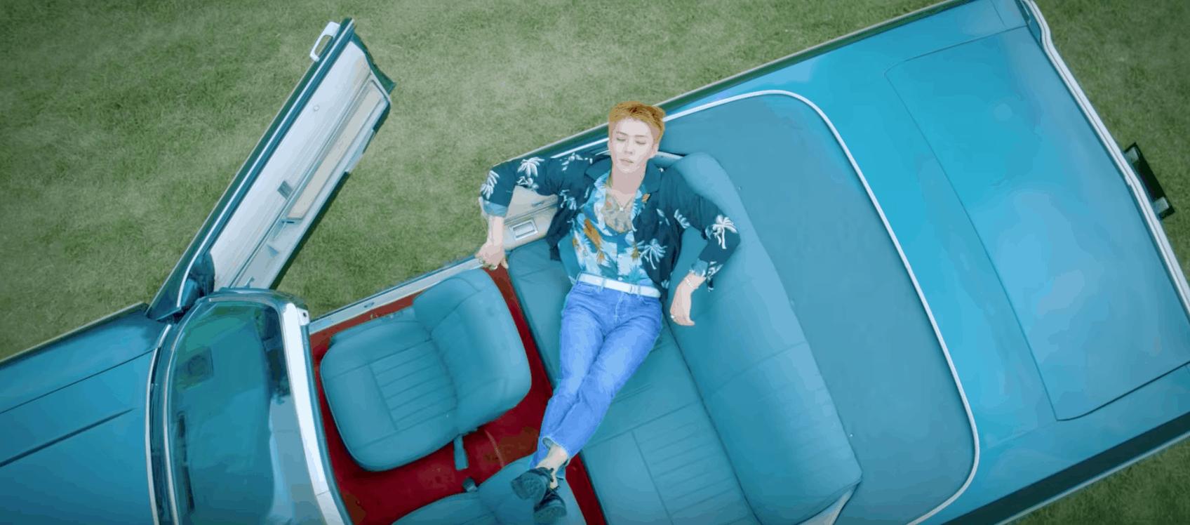 EXO Ko Ko Bop Video - Redheaded member sitting in a blue convertible car