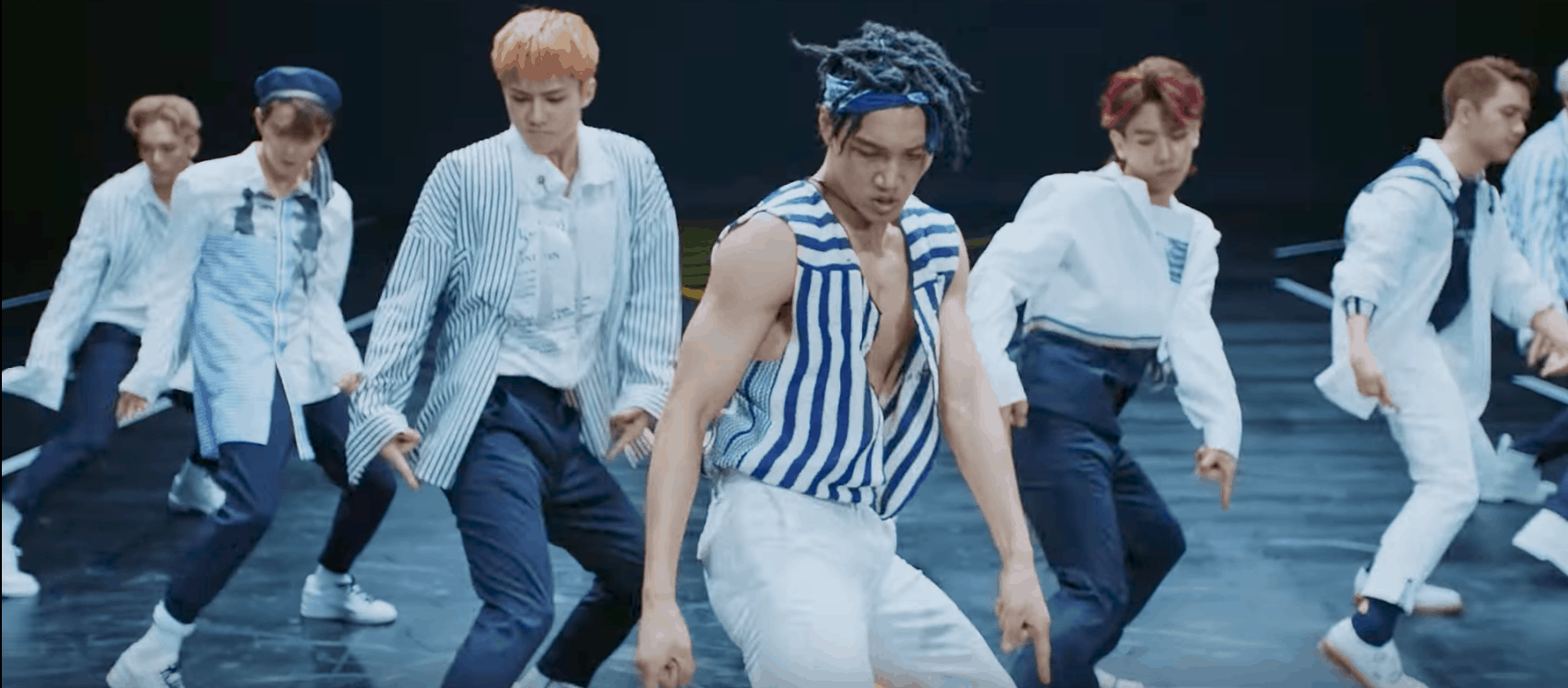 EXO Ko Ko Bop Video - the boys doing a dance routine wearing striped shirts and navy pants