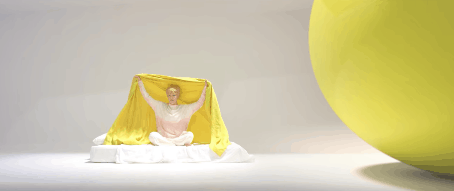 BTS Serendipity music video: Band member on a white floor covered with a bright yellow sheet, sitting next to an oversized yellow ball