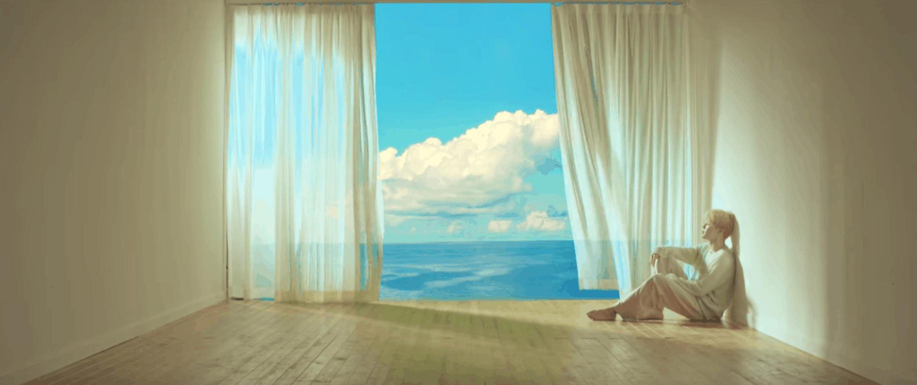 BTS Serendipity music video: Shot of the lead singer sitting on the floor in a room next to a big open window overlooking the ocean