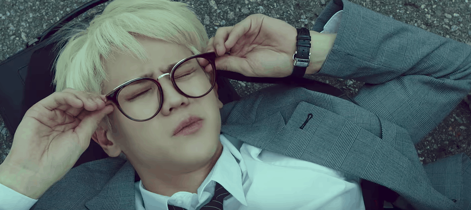 Highlight can be better music video - screenshot of band member with blond hair wearing glasses and lying on the ground