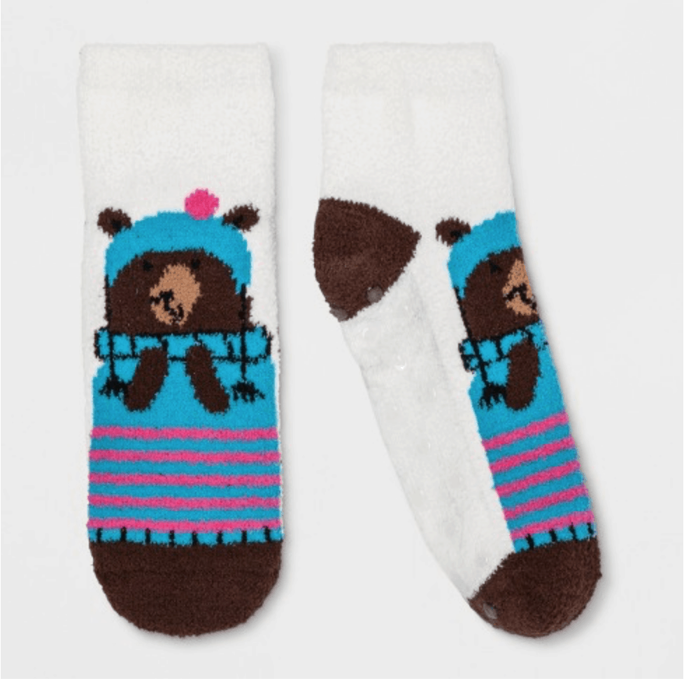 White fuzzy socks with brown bear in a blue jacket