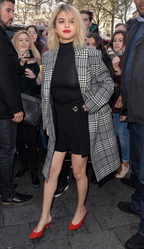 Celebrity red shoes outfit: Selena Gomez wearing a black ribbed turtleneck, a black mini skirt with a metal detail, a gray and black plaid long coat, and red mules