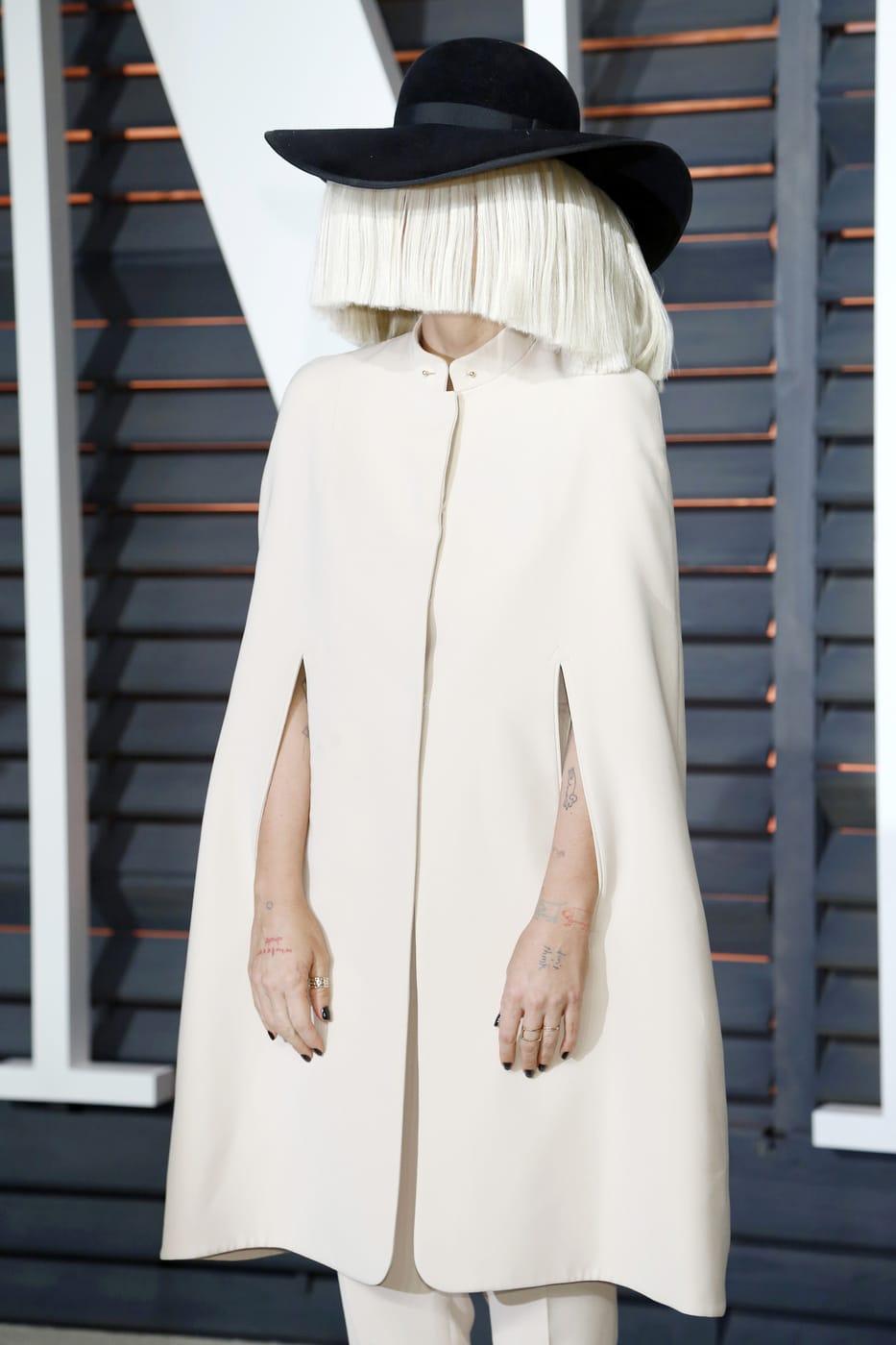 Sia in a cream colored cape coat and black hat