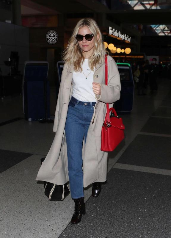 Sienna Miller wearing a beige long coat, white t-shirt, chunky sunglasses, a red satchel shoulder strap bag, spliced straight leg jeans, and black lace-up booties