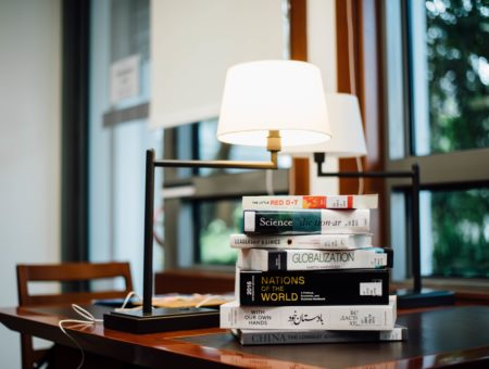 Stack of books on a desk with a lamp