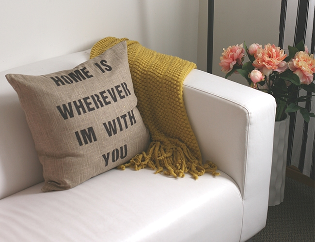 Photo of a stenciled pillow on a white couch with a yellow blanket on it. There is a vase of flowers next to the couch.