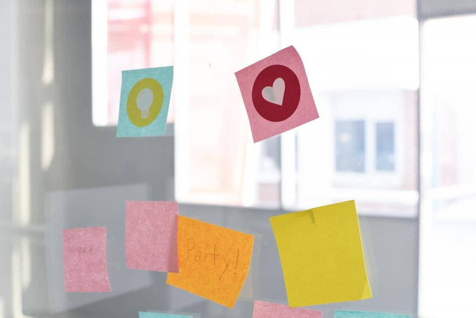 Pink, blue, orange, and yellow sticky notes on a window