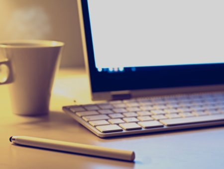 How to make yourself study: Photo of a hot drink next to computer
