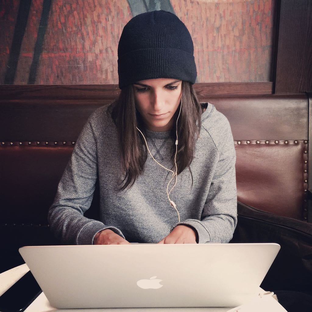 Girl in beanie watching something on laptop