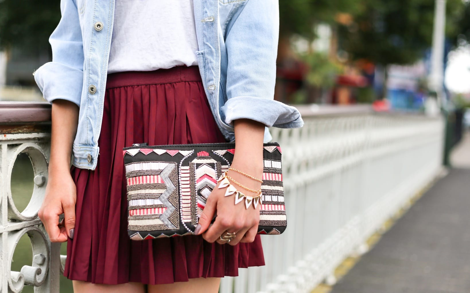 How to wear a graphic tee - girl wearing a pleated skirt, light wash denim chambray shirt, and graphic tee shirt with bracelets and a patterned clutch