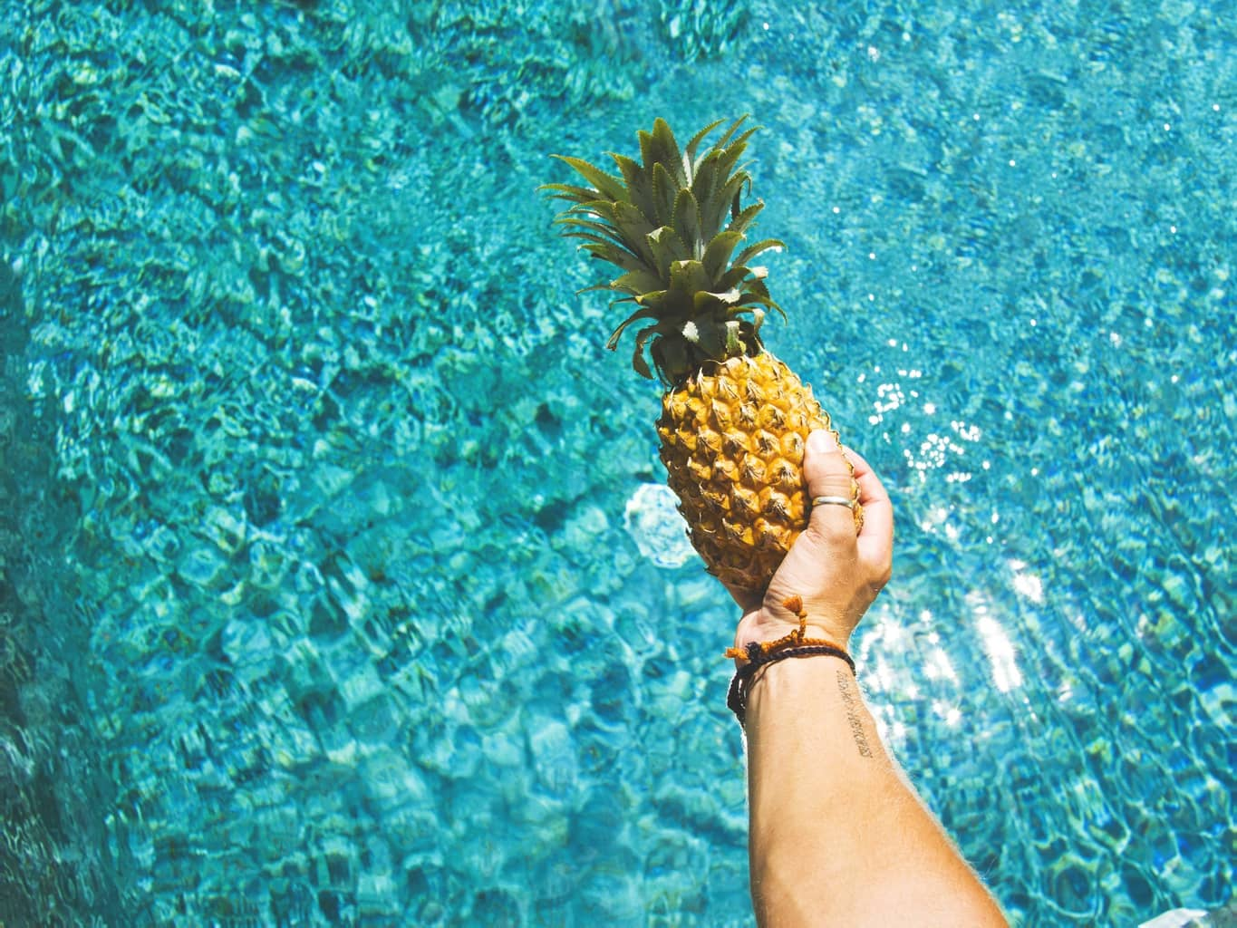 Person holding a pineapple over a pool