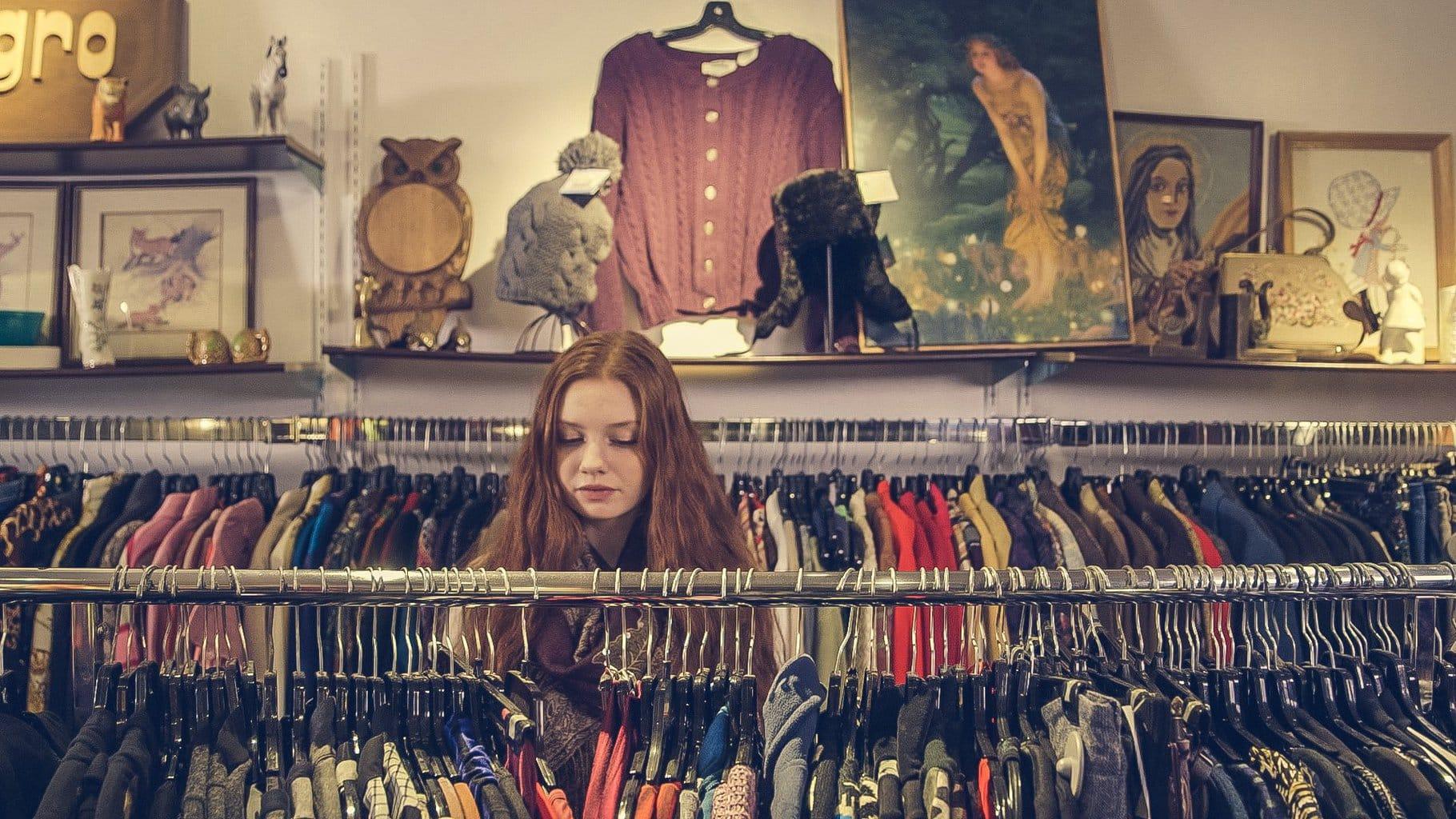 Girl looking through racks of clothing.