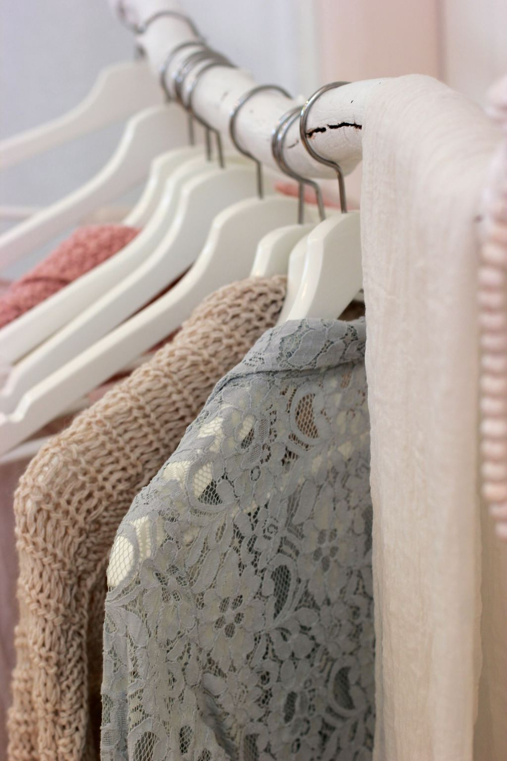 Photo of several pastel-colored clothing items on hangers