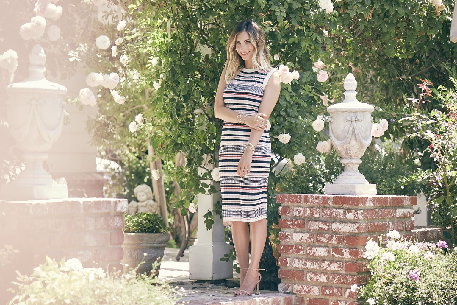 Emily from Cupcakes and Cashmere wears a multicolored striped dress