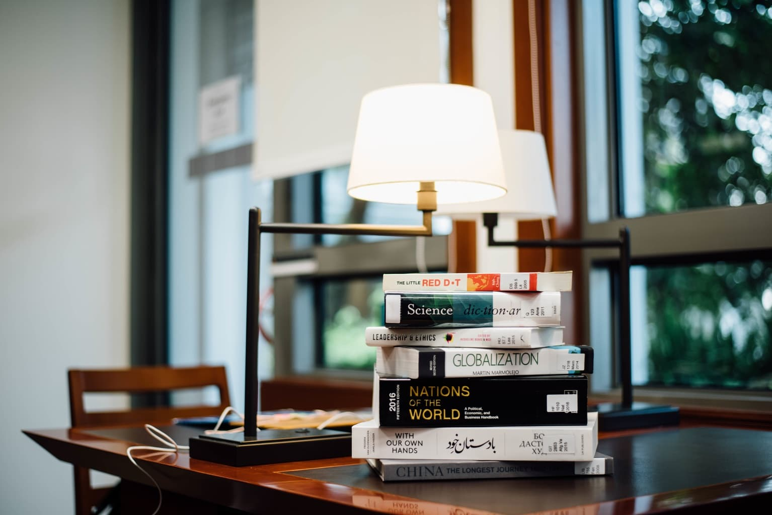 table with stacks of books in a naturally lit studying area