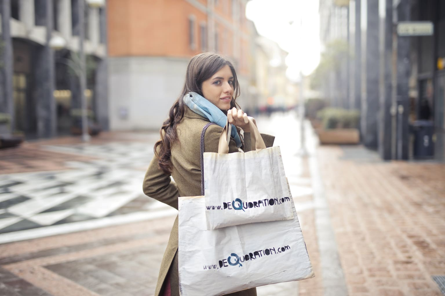 Photo of woman walking down the street looking over her shoulder while holding two shopping bags and wearing a coat and scarf
