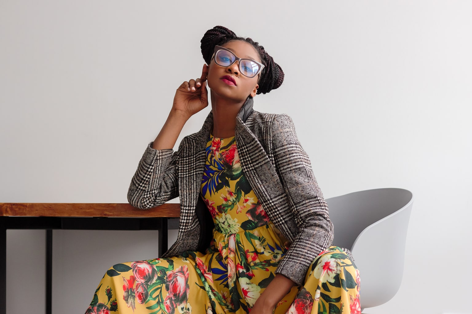 Woman sitting at a table wearing glasses, a long yellow floral dress, and a gray plaid blazer