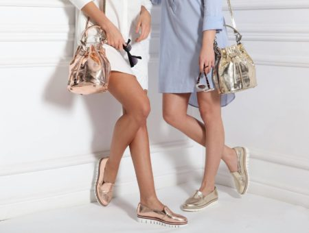 Shot of two women from the waist down wearing shirt-dresses and metallic bucket bags and loafers, and holding sunglasses