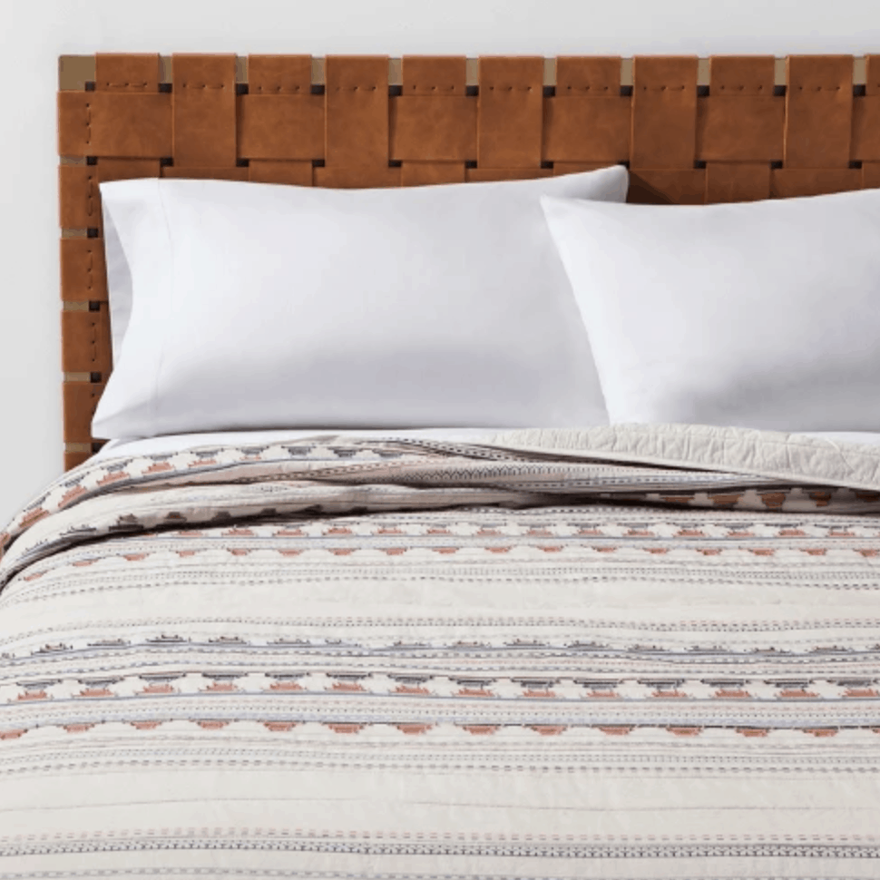 This simple cream jacquard Target quilt has a coral and blue striped pattern.