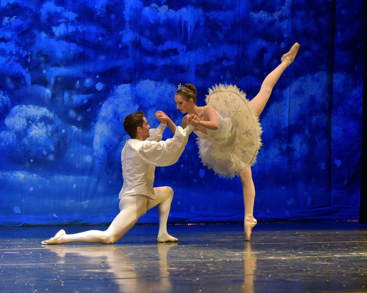 Two dancers, one man and one woman, in front of a blue backdrop in The Nutcracker Ballet